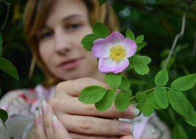 Frau mit Hagebuttenblüte